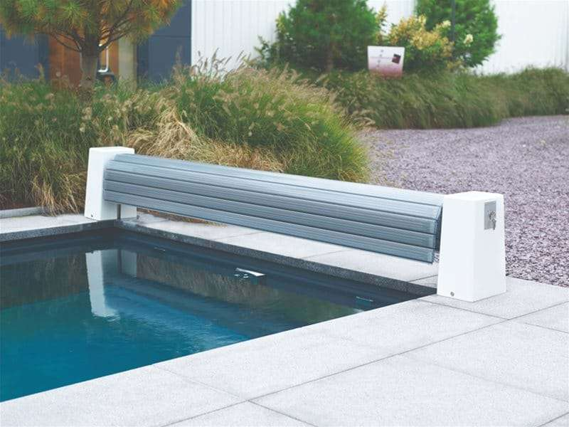 automatic slatted pool cover open at the end of a one piece swimming pool.