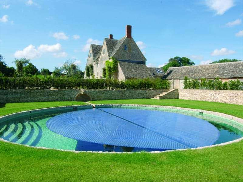 automatic slatted pool cover half open over a swimming pool.