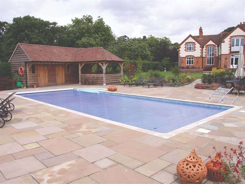 one piece swimming pool with an automatic slatted pool cover.