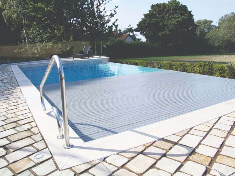 automatic slatted pool cover half open over a one piece swimming pool.