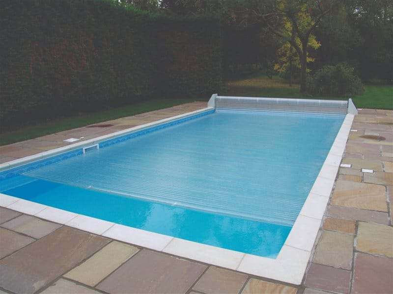 automatic slatted pool cover nearly fully covering one piece swimming pool.
