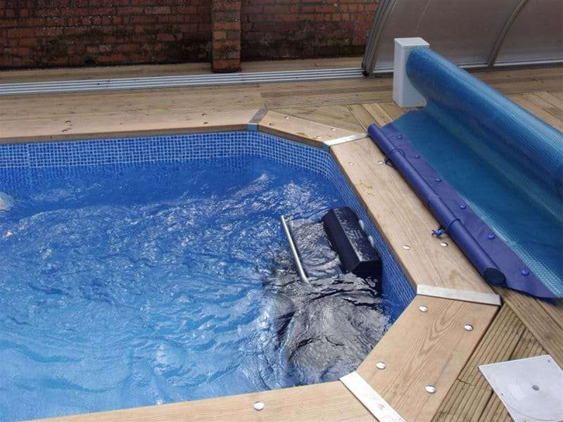 fastlane swimming machine in small one piece swimming pool with a pool cover.
