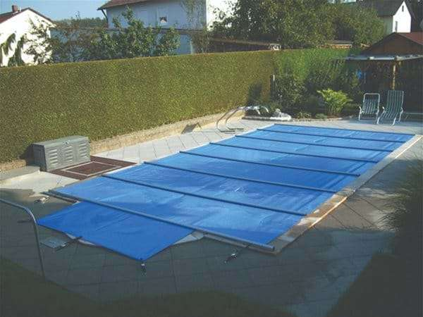 manual safety pool cover, covering a one piece swimming pool.