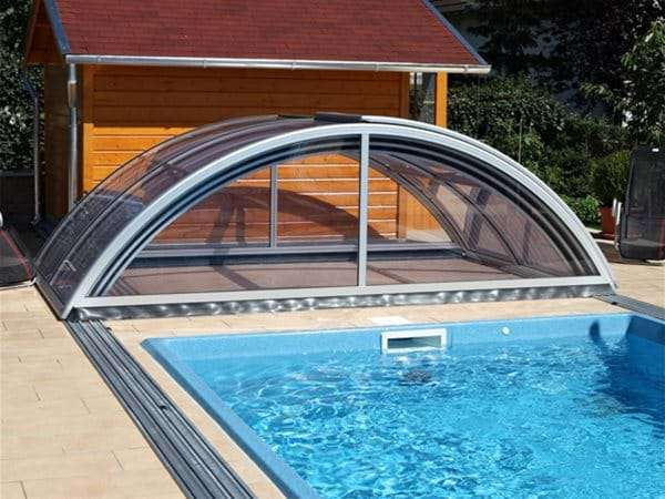 one piece swimming pool with sun or sky pool enclosure retracted.